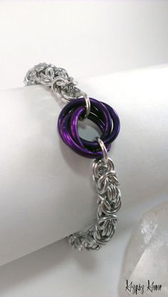 Chainmaille bracelet with purple mobius flower.