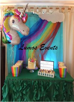 Helium filled unicorn balloon with rainbow and cloud backdrop, curly willow green tablecloths, lightbox, rainbow bags filled with sweet or salt popcorn.