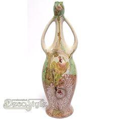 Plateel Vaas Colenbrander Motief Papegaai  Plateel vaas met prachtige warme kleuren Er staat een papegaai op afgebeeld in warme kleuren groen en bruin waardoor het een opvallende object wordt in uw collectie.  Ook de vormgeving is heel apart. De twee oren geven de vaas het uiterlijk van een kruik.  De vormgeving die niet rond, maar wat ovaal is, maakt dat de vaas ook op een smallere plek kan staan. De afbeelding op deze vaas is in relief ingebakken.