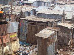 What if we invited them in to the slum? We could add an entrance to the tent that looks like one of these shacks and have some 'garbage' eloquently arranged around the entrance. We could use fabrics from the other pictures (bright, patterned cotton fabric as table covers over dark blue) and use grass skirts as table skirts. Candles in beaded or mercury glass will set a nice tone