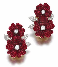 Pair of ruby and diamond ear clips, 'Pergola Royale', Van Cleef & Arpels, 1996. Each featuring two flowers, the petals composed of calibré-cut rubies en serti mystérieux, the leaves and pistils set with brilliant-cut diamonds, each signed V.C.A., numbered, French assay and maker's marks, case by Van Cleef & Arpels. Sotheby's.