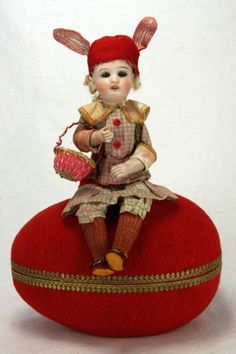 Antique German Easter Candy Container,with a Porcelain Doll with rabbit ears and holding a basket,on a Egg.
