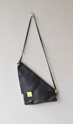 Very cool vintage 1980s soft black leather shoulder bag in uneven triangle shape with brass lock closure, large flap, inner zip pocket and long, cross-body strap.  --- M E A S U R E M E N T S ---  15 x 11 strap length: 41 maker/brand: n/a condition: excellent  ➸ More vintage bags http://www.etsy.com/shop/DearGolden?section_id=10308208  ➸ Visit the shop http://www.DearGolden.etsy.com _____________________  ➸ instagram | deargolden ➸ twitter | deargolden ➸ facebook.com | deargolden ➸ blog…