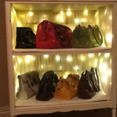 Purse display I made from an old dresser.The lining is made from the silk chiffon chair covers I made for my daughters wedding.