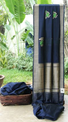 This deep blue Benares silk has large bhuttas in shamrock green, emerald green, gold and silver zari. The pallu and border have an intricate weave of gold zari making it unique and beautiful