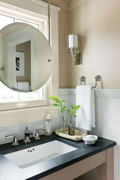 in the small bath a mirror is suspended with metal rods in front of the - Bathroom Sink And Mirror