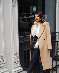 Pam Hetlinger pairs high waisted striped navy trousers with a white turtle neck sweater and a camel suede coat
