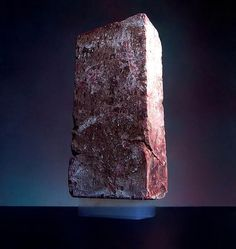 This picture is of a 2.5kg brick supported by a piece of aerogel, the worlds lightest solid material. This particular piece weighs in with a mass of 2 grams.   Aerogel is nicknamed 'frozen smoke' or 'solid air', due to the fact that it is composed of 99.98% air by volume. Aerogels are a diverse class of amazing materials with properties unlike anything else known. They exhibit the lowest thermal conductivity of any known solid, and are the lowest density structural materials ever developed.