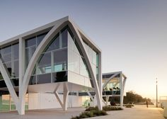 Steel arcs curve across the glass facade of this Portuguese marina complex.