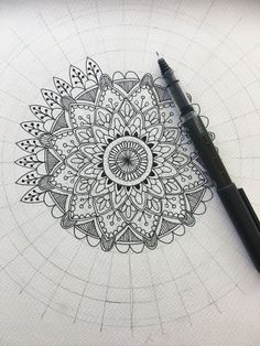 Starting a hand drawn mandala pattern using a compass and protractor to mark out the circles and symmetry.