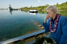 """Velma Stratton, wife of USS Arizona Survivor Donald Stratton looks over the side of the USS Arizona Memorial as ceremonial flowers float over the sunken ship at the 69th Pearl Harbor Remembrance Day, December 6, 2010.  """"The myth is, the Arizona will stop leaking oil once all her shipmates have returned,"""" says Velma."""