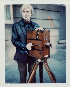 Andy Warhol (American, 1928-1987)    Self-Portrait with Movie Camera, ca. 1971    Polaroid™ Polacolor Type 108    4 1/4 x 3 3/8 in. (10.8 x 8.6 cm.)    The Andy Warhol Museum, Pittsburgh; Founding Collection, Contribution The Andy Warhol Foundation for the Visual Arts, Inc.    © The Andy Warhol Foundation for the Visual Arts, Inc.    1998.3.8902