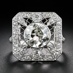 This early-nineteenth century Edwardian knockout shines front and center with a super-scintillating European-cut diamond, weighing 2.20 carats. The gorgeous center diamond sparkles from within a platinum bezel setting atop delicate Spirograph-style latticework. The diamond is accompanied north and south by a couple of smaller friends and geometrically framed with small old mine-cut diamonds that continue down the ring shank. This rare, radiant and remarkable antique jewel - circa 1915-1920