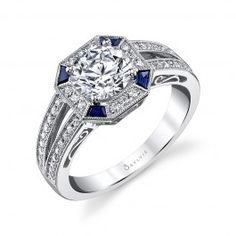 Silvie Collection offers this gorgeous vintage inspired engagement ring, with a 1.25 carat round brilliant diamond center surrounded by an octagon shaped halo of gorgeous deep blue sapphire baguettes and round diamonds held by milgrain accented borders, with more channeled round diamonds (0.48 ct. tw.) on the split shank, again with milgrain detailing. Altogether, a masterpiece of design and skill and a flattering fashionable piece of jewelry. www.diamonds.pro
