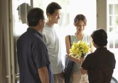 Parents greeting adult offspring at front door - Pinnacle Pictures/Iconica/Getty Images