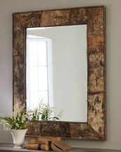 "Complimenting the metal sculptured entry table is the Birch Bark Mirror. A thin ribbed-rattan overlay on a birch bark frame adds rustic appeal to this beveled mirror. Imported.  Frame made of birch veneers and wood composite.  Beveled mirror measures with frame 29""W x 39""T."