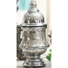 """$29.95, Etched Mercury Glass Jar with Lid  Item #   CC0907  This gorgeous jar is made of antiqued mercury glass with etched patterns around the body and the lid. The shape is classic and elegant, and this jar can be used to store many sorts of things, but it should not be used with food. Made by Creative Co-op, this lid with jar measures about 8"""" tall."""
