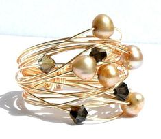 Gold Pearl Wire Wrap Ring / Gold Nest Pearl Ring / Wire Wrapped Ring with Gold Wire Freshwater Pearls and Black Diamond Swarovski Crystals This ring is from a series of wire wrapped rings Ive made recently. Influenced by my modern surroundings from moving to Germany and their modern