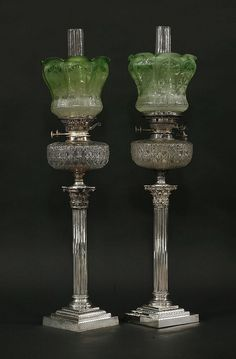 A pair of Victorian silver-plated Corinthian column oil lamps, with cut glass reservoirs, and etche