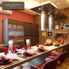 Cozinha em cimentado tom concreto e assessórios em aço inox tendo como destaque parede em pastilha de vidro cor vermelha. Os tons vermelhos foram usados também nas cadeiras, louças e nas panelas trazendo aconchego ao ambiente.