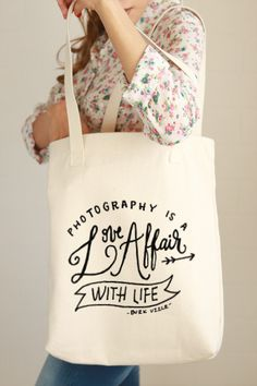 """Hand drawn lettering quoting: """"Photography is a Love Affair with Life"""" by Burk Uzzle. A great tote bag for daily use! - 12.0 oz., 100% cotton canvas - 22"""" handles - Reinforced bottom - The design is p"""