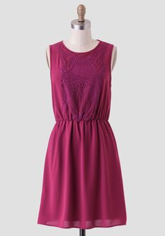 This adorable berry-colored dress is designed with a mesh overlay at the bust with ornate embroidery.