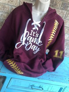 It's Game Day Hoodie with lace up front and baseball laces on the sides Softball Mom, Baseball Mom, White Lace, Lace Up, Up Front, Kangaroo Pouch, Sports Mom, White Hoodie, Mom Shirts