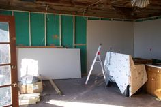 Guest house during reconstruction.You are looking at the kitchen, the corner is where you later see a corner shaped,wall cabinet, the original front door is waiting to be painted. Drywall waiting to be hung and spackled and painted.