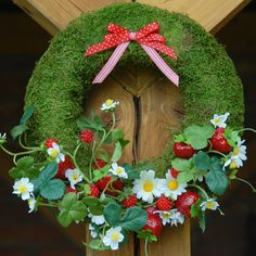 Jahodový věnec Mechový korpus je zdoben dokonalými jahodami a kopretinami. Krásná letní dekorace do Vašeho domova Průměr 30 cm kód 917