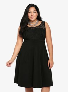 A delicate black lace bodice plays nicely with a flirty solid black swing skirt on this stunning dress. Darling and daring, it's your new little black dress with a twist.