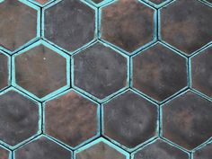 Handmade industrial style hexagonal tile, finished in a raku kiln with turquoise borders.