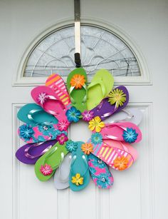 "Flip Flop Fun, Decorate your door or room with the summer footwear we love to wear. This wreath is fastened with greening pins making it sturdy and heat resistant. The wreath measures approximately 24"" across, includes 16 youth flip flops and comes with a variety of flower embellishment's and large rhinestones. Please avoid displaying this wreath in between a storm and house door. Too much direct sunlight causes extreme heat built up."