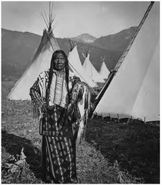Chief Charlot fulllength portrait standing facing front with tipis behind him Flathead Reservation Montana 1908 North American Indian Tribes, Native American History, Native American Indians, American Symbols, Native American Pictures, Native Indian, Blackfoot Indian, Historical Pictures, Before Us