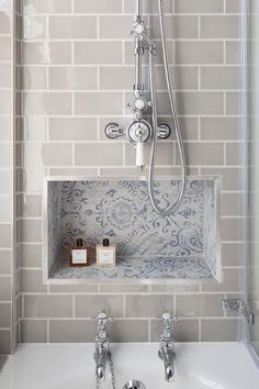 Gray subway tiles frame a blue mosaic tiled niche located below a polished nickel exposed shower kit and above a drop-in tub with polished nickel tub fillers.