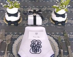 a beautiful dark blue and crisp white place setting with monogrammed napkins