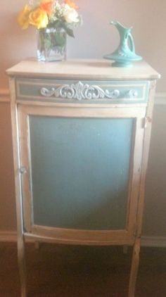 The door is painted in the delightful color of Duck Egg Blue. All other parts of the cabinet are painted Old White, distressed, and then hand waxed to completely seal and protect this old piece.