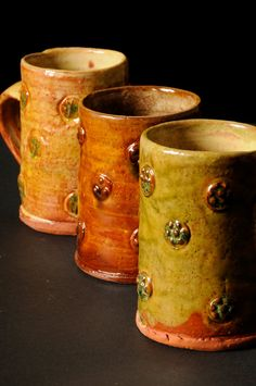 lead glazed, slipped and sprigged mugs...............doug fitch.  SERIES
