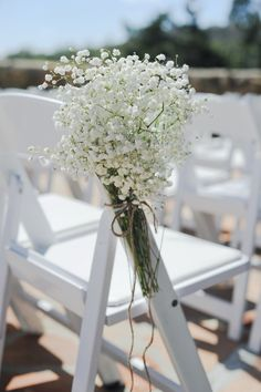 Baby's breath bouquets tied to chairs Photo by: continuumweddings.com