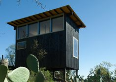 Charred Cabin by DRAA is a blackened timber shelter on stilts