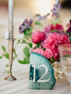 """""""Instead of paper table signs, we used agate bookends in shades of pink, blue, and purple with white lettering as table numbers. Now we have two very heavy boxes filled with agate in our garage."""" Lily Waronker and Jonny Gordon's Wedding in Los Angeles"""