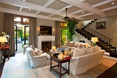 they painted the beams white and the ceiling in a soothing shade of greige, the beautiful staircase with black trim.