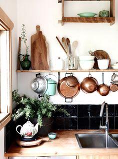 Copper pots organized in white kitchen