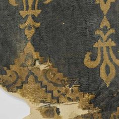 Fragment of yellow and black silk with repeating pattern of fleurs de lis and zigzag bands, alternately in positive and negative colors. The zigzag bands Arabic letters. Incomplete report. pasted on cardboardc. 1175 - c. 1225 - Rijksmuseum