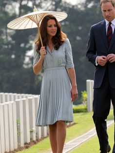 Kate is pretty with parasol and pleats.