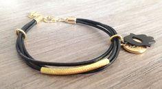 Pulsera de piel negra con detalles dorados y una #hamsa #amuletbb