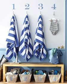 Banish prebeach pandemonium (Who took my towel? Where are my flip-flops?) with a designated station   featuring boldly numbered hooks and corresponding cloth baskets for each guest or family member. Need this by the back door to the pool!