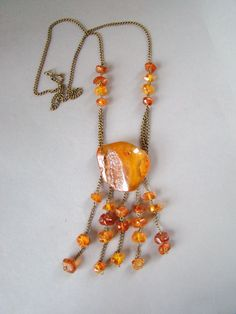 Stylish estate necklace made with antique amber. The central chunk of amber measures aprox 1 7/8 x 1 5/8. There are 26 more hand cut amber beads in