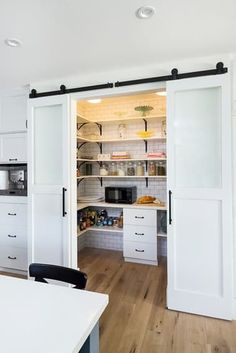 Trying to squeeze a small pantry into a kitchen? Save some space and create a really cool element by using a sliding barn door to hide the pantry, or the laundry, or coffee station — anything in a closet. These sliding barn doors have become so popular lately — here are 10 great examples of barn doors in the kitchen.
