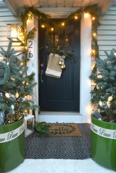A darling small Christmas entry complete with planted evergreens, lights, and garland draping the front door for a festive holiday entryway! Christmas House Lights, Noel Christmas, Christmas Decorations, Christmas Ideas, Christmas Porch, French Christmas, Christmas Music, Christmas Crafts, Cape Style Homes