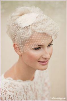 Entzückende Federbrosche in hellem Creme, creme farbene Federn sind Mittelpunkt des Haarschmuckes. Befestigt ist die Brosche an einem creme farbenen Reif. Zusätzlich fließt Hutnetz heraus und setzt...